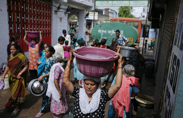 A woman carries a bucket filled with drinking water after collecting it from local government supply truck in Ahmedabad