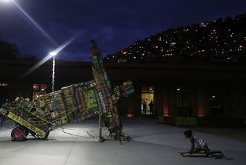 A girl plays with a skateboard next to a work by Mundano during the Art Rua street art festival in Rio de Janeiro