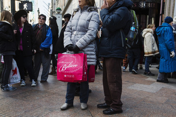 Pedestrians carry shopping bags as they walk down the street during Black Friday sales in New York