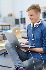 junger mann im büro mit laptop und kopfhörern