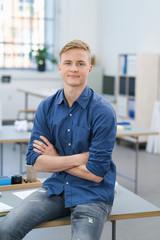 selbstbewusster junger mann sitzt im büro auf dem schreibtisch