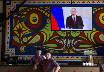 Staff watch a speech by Russian President Putin at a pizza restaurant in Simferopol