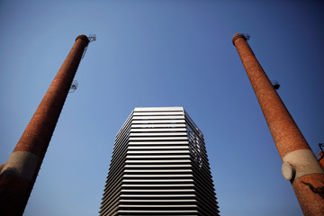 The Smog Free Tower, the world's largest smog vacuum cleaner designed by Dutch artist and innovator Daan Roosegaarde is seen between chimneys as the artist presents his The Smog Free Project at D-751 art zone in Beijing