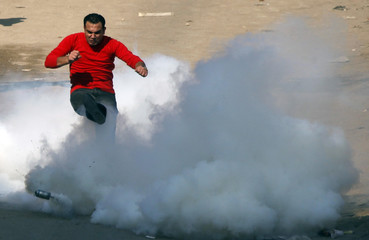 An Orthodox Coptic Christian kicks a gas canister during clashes with riot police in Cairo