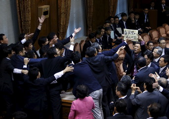 Japan's lawmaker Yamamoto of The People's Life Party & Taro Yamamoto and Friends holds a placard as lawmakers crowd around Yoshitada Konoike, chairman of the upper house special committee on security, at the parliament in Tokyo,