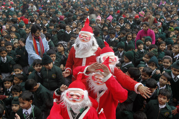 Students dressed as Santa Claus distribute sweets among children during a Christmas celebration at a school in Chandigarh