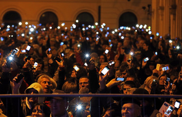 People holds up their mobile phones as they protest against new tax on Internet data transfers in centre of Budapest