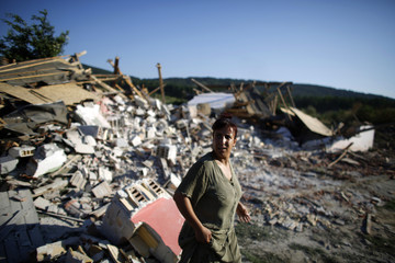 Bulgarian Roma woman walks amidst rubble of house after it was demolished in Roma suburb in city of Stara Zagora