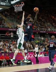 James of the U.S. goes in for a lay-up as Lithuania's Pocius guards while Bryant of the U.S. looks on during their men's preliminary round Group A basketball match at the Basketball Arena during the London 2012 Olympic Games