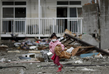 Girl walks with her teddy bear, which she retrieved from her house destroyed by the March 11 earthquake and tsunami, in Ishinomaki