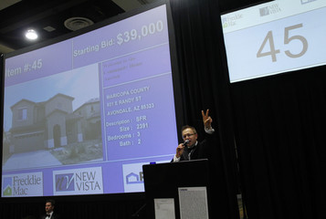 Auctioneer Mark Buleziuk auctions off a house during the Freddie Mac foreclosed home auction at the Phoenix Convention Center in Phoenix