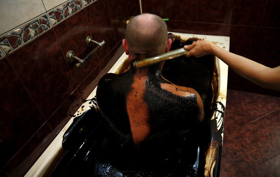 A man gets his back cleaned of crude oil as he lies in a bathtub during a health therapy session at Naftalan Health Center in Baku