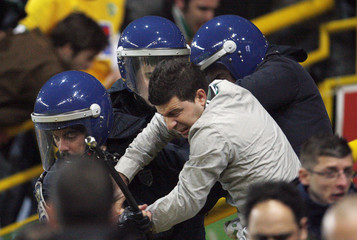 Anti-riot policemen try to control a Sporting supporter during their soccer match against Benfica for the Portuguese Premier League in Lisbon