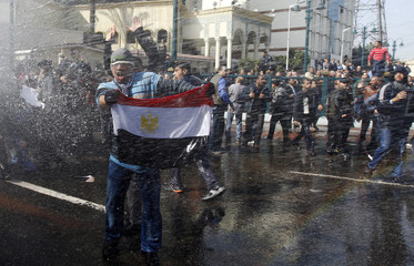 A protester holds an Egyptian flag as he stands in front of water canons during clashes in Cairo