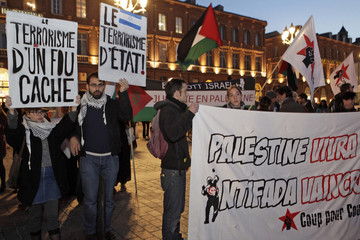 """Pro-Palestinian supporters hold placards one which reads, """"State Terrorism"""" as they demonstrate in the Place du Capitole in Toulouse"""