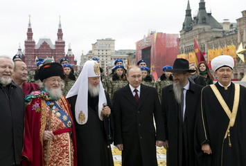 Russian President Putin poses for a photo with Russia's religious leaders during flower-laying ceremony on National Unity Day in Red Square in Moscow
