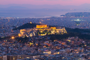 cityscape of Athens with illuminated Acropolis hill, Pathenon and sea at night, Greece