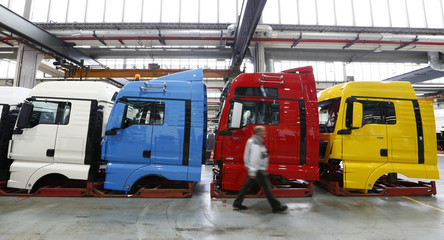 A man walks past driver cabins in the truck production plant of German truck and bus-maker MAN AG in Munich