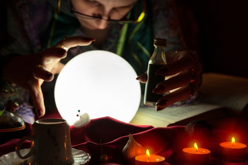 Crystal ball and love potion in hands of fortune teller woman