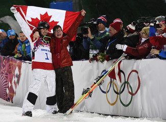 Winner Canada's Alex Bilodeau and brother Frederic celebrate with Canadian flag after men's freestyle moguls competition at 2014 Sochi Winter Olympic Games in Rosa Khutor