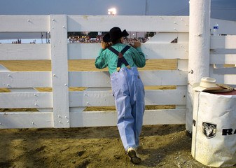 Rodeo clown Dusty Barrett looks through the gate into the arena at the Cowtown Rodeo in Woodstown New Jersey