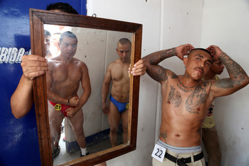 Inmate flex their muscles while posing for a picture as other look at himself in a mirror before a bodybuilding contest at a prison in Atlacholoaya