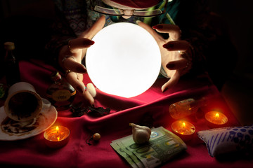 Fortune teller woman looking at crystal ball with her hands around crystal ball