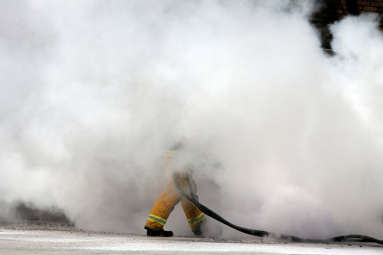 A firefighter is engulfed in smoke while dousing a burning car at the entrance to the Lincoln Tunnel that caused the closure of the tunnel snarling Friday rush hour traffic in New York