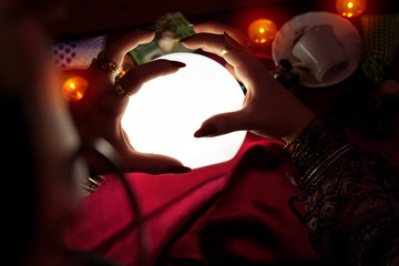 Crystal ball with hands of fortune teller woman