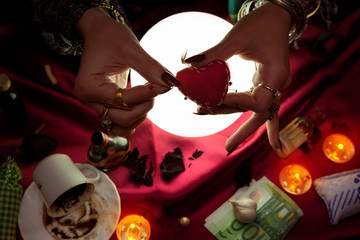 Fortune teller woman holding little heart for witchcraft