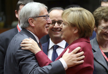 Juncker, the incoming president of the European Commission, greets Germany's Chancellor Merkel next to France's President Hollande during an EU leaders summit in Brussels