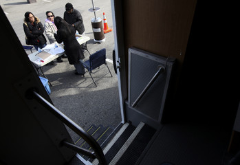 People speak with banking advisors outside the New York State Department of Financial Services Foreclosure Relief Unit in Brentwood, New York