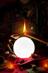 Crystal ball, candle and hand of gypsy fortune teller woman