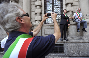 Mayors pose for a picture during a protest against the government's austerity package in downtown Milan