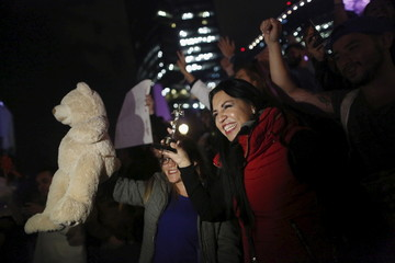 """Fans hold a teddy bear and a replica Oscar as they celebrate the win by Inarritu for Best Director and DiCaprio for Best Actor in his leading role for the movie """"The Revenant"""" at the 88th Academy Awards in Hollywood, in Mexico City"""