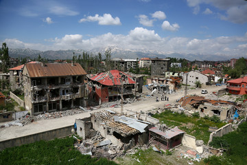 Residents walk past buildings which were damaged during security operations and clashes between Turkish security forces and Kurdish militants, in Yuksekova in the southeastern Hakkari province