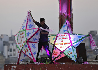 A man installs Christmas decorations atop a church on the eve of the Christmas in Ahmedabad