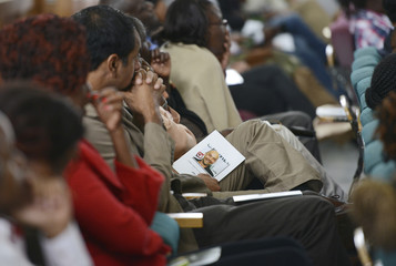 Mourners follow proceedings during the funeral service for Carey Eaton in Nairobi