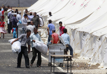 Syrian refugees walk along their tents at a refugee camp in the Turkish border town of Reyhanli