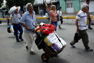 A man push a trolley with toilet paper and other goods as he walks towards  the Colombian-Venezuelan border after shopping in Cucuta, Colombia