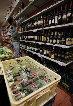 A shop owner removes bottles of hard liquor from a shelf in Prague