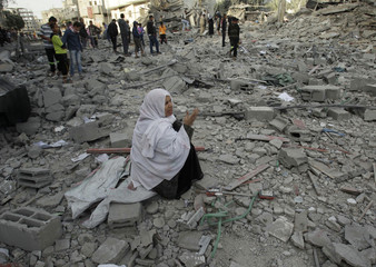 A Palestinian woman reacts as she sits on the rubble of her destroyed house after an Israeli air strike in Rafah in southern Gaza Strip