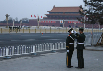 A paramilitary policeman adjusts the hat for his colleague near the Tiananmen Square, prior to the opening ceremony of National People's Congress in Beijing