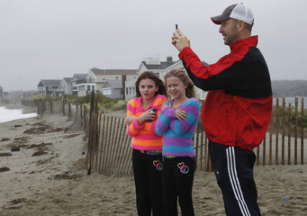 Girls shiver as they stand beside a man taking a picture of the ocean, shortly before the arrival of Hurricane Sandy in Scituate