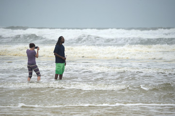 Kelly Unwin (L) photographs Doniell Turner in the surf as a band of Hurricane Matthew arrives in Daytona Beach