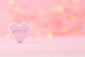 Pastel colored candy hearts in a bokeh background.