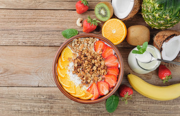 Granola with Greek yoghurt and fruit on a wooden background in a rustic style