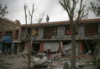 A man stands on the roof top of shops damaged in bomb blasts in Kabul