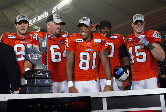 Lions players stand behind the Western Division championship trophy during their Western Conference Final football game in Vancouver
