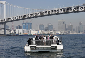 Denmark's Crown Prince Frederik and his wife Crown Princess Mary pose for photos in front of the Rainbow Bridge as they take a boat trip in Tokyo Bay for briefing on preparations for the Olympic Games in 2020 in Tokyo